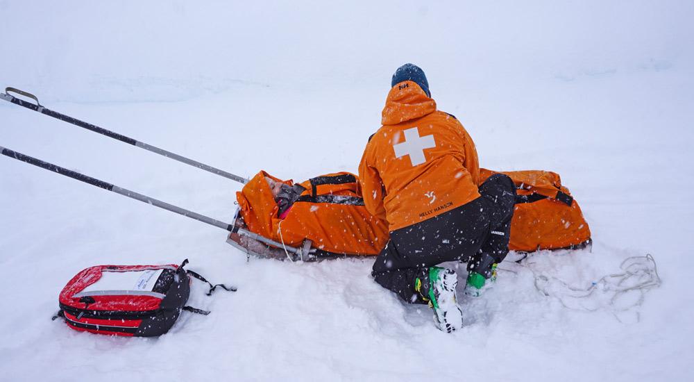 Nico verpackt ein Unfallopfer in den Rettungsschlitten