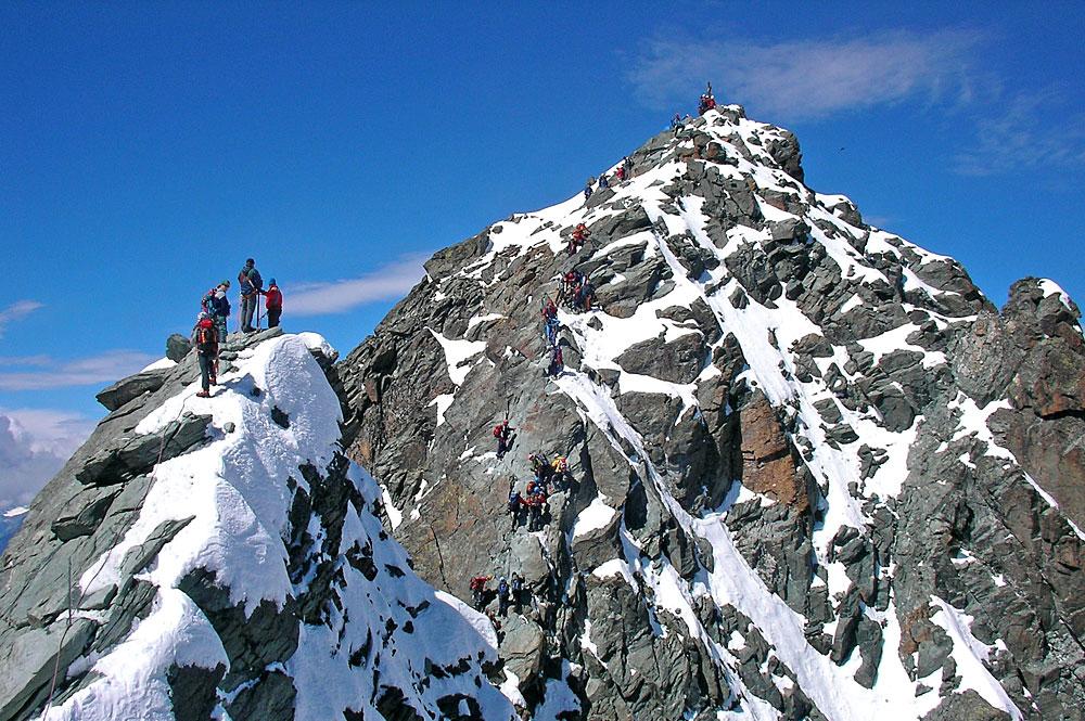 Bergsteiger auf dem Gipfel des Kleinglockners, im Hintergrund der Großglockner
