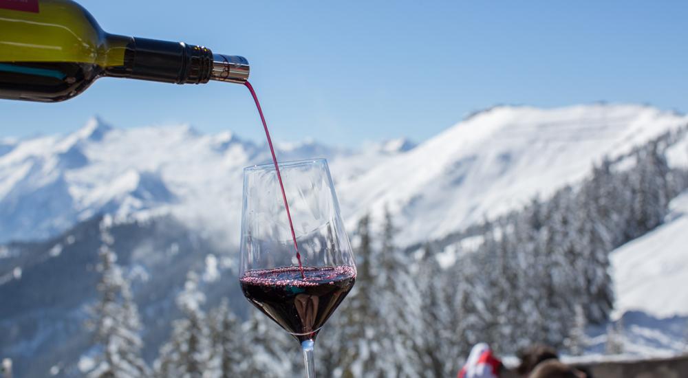 Flasche gießt Wein in ein Glas auf der Schmitten