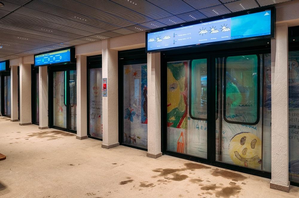 Bahnsteig mit den vollautomatischen Glastüren, im Hintergrund visualisierte Waggons
