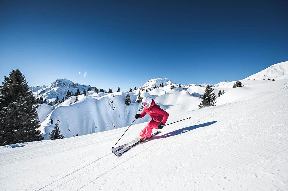 Skifahrer auf einer sonnenbeschienenen Piste in Lech Zürs