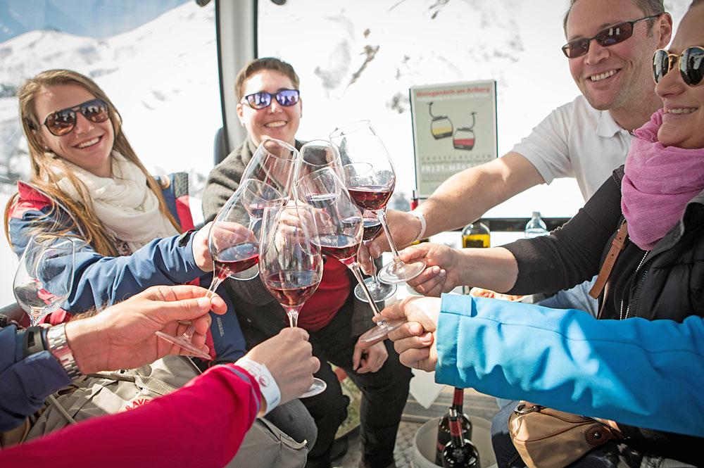 Wintersportler trinken Wein in der Gondel