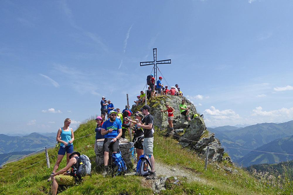 Wandergruppe an einem Gipfelkreuz bei der kitzalp24