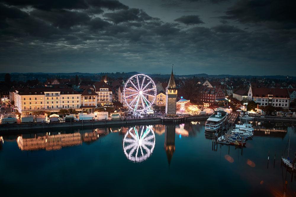 Beleuchtetes Riesenrad im Hafen von Lindau