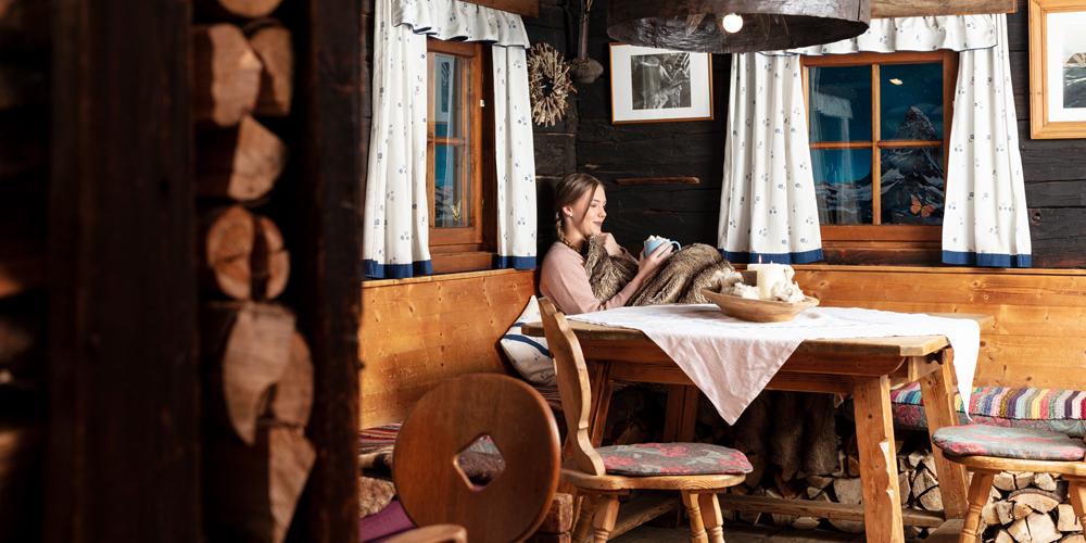 Frau beim gemütlichen Entspannen in einer Almhütte