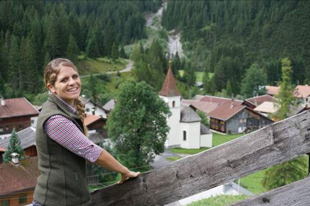 Eine Junge Frau und im Hintergrund ein Dorf im Lechtal