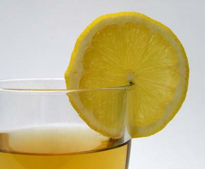 Ein Glas heiße Zitrone mit Zitronenscheibe am Glasrand