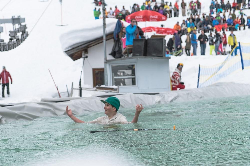Mann schwimmt im Eissee bei beim Watersurf Contest in See