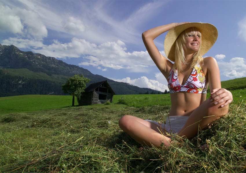Frau sitzt auf einer duftenden Heuwiese in der Steiermark