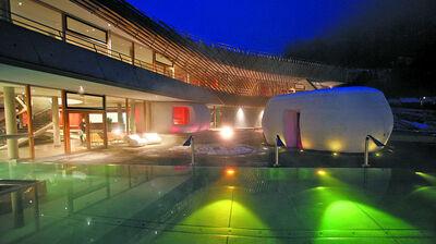 Außenansicht des Römerbads Bad Kleinkirchheim mit Außenpools bei Nacht