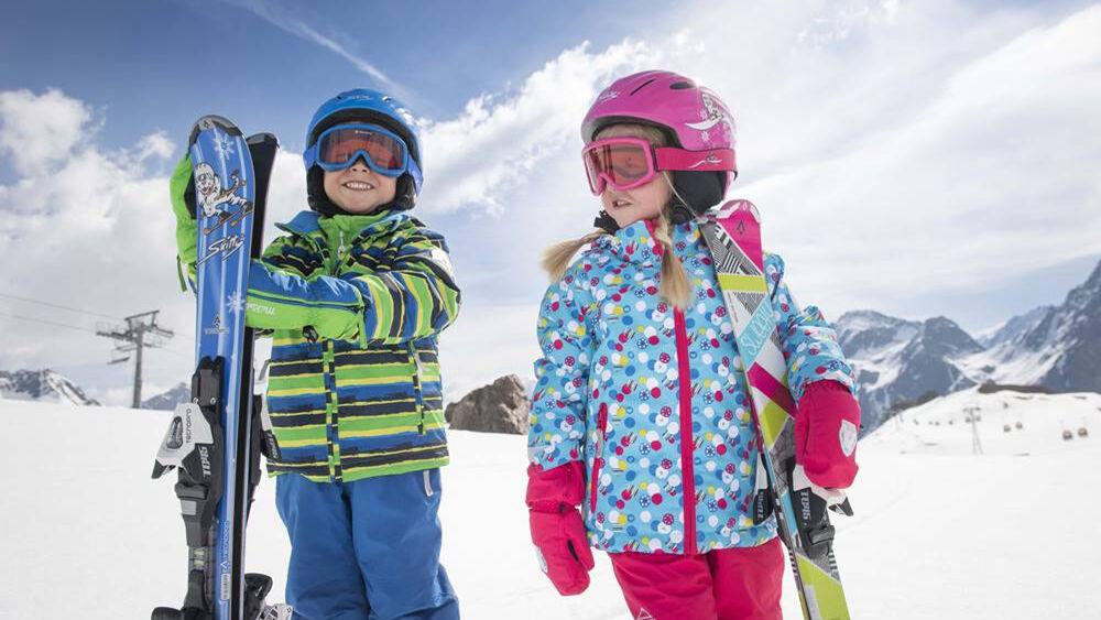 Kinder beim Skifahren im Schnee mit Skihelm
