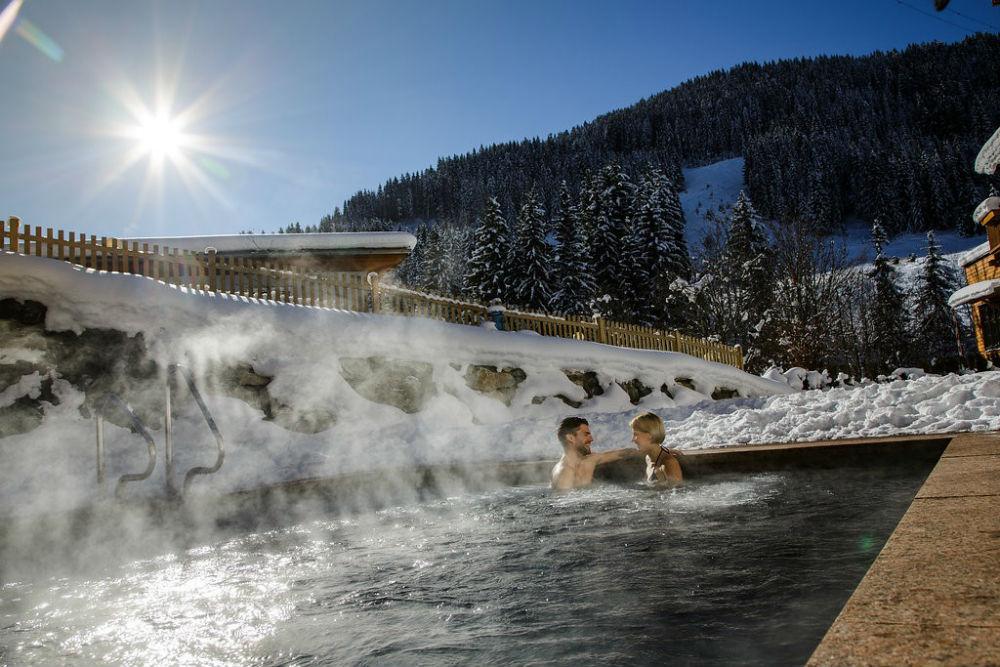 Hotelgäste im beheizten Outdoor-Pool vom Sporthotel Wagrain im Winter