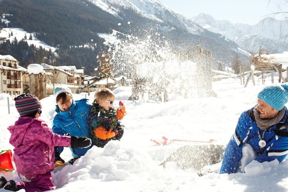 Kinder spielen im Schnee vorm ROBINSON Club Amadé