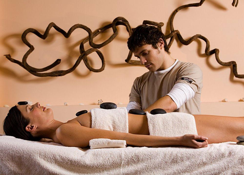 Eine Frau genießt eine Hot Stone Behandlung im MOHR life resort