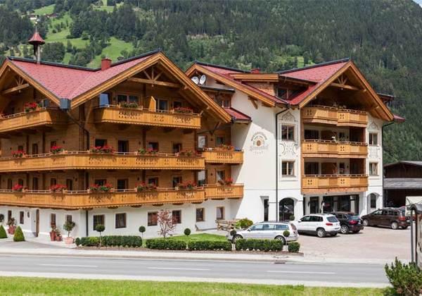 Hausansicht Ferienhotel Sonnenhof, im Hintergrund die beleuchtete Talabfahrt