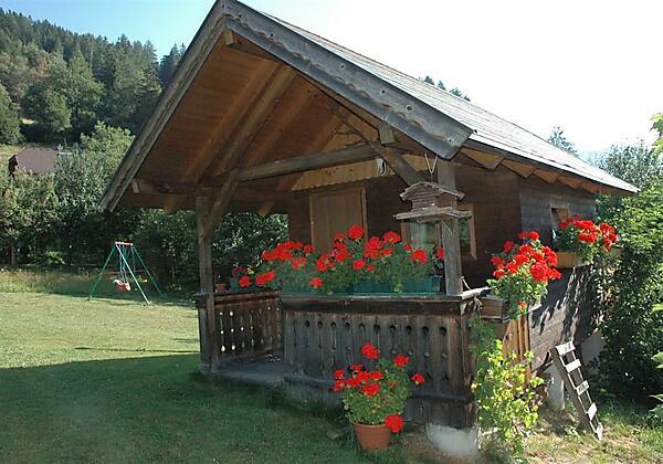 Gartenhütte mit Schaukel im Hintergrund
